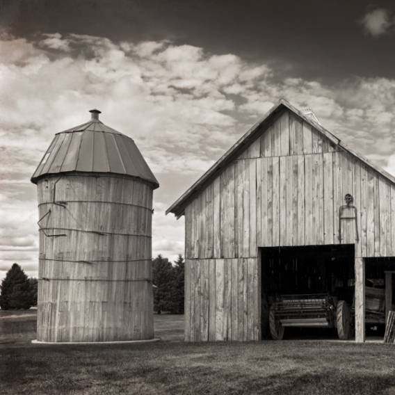 Greyscale image of a rustic barn and silo